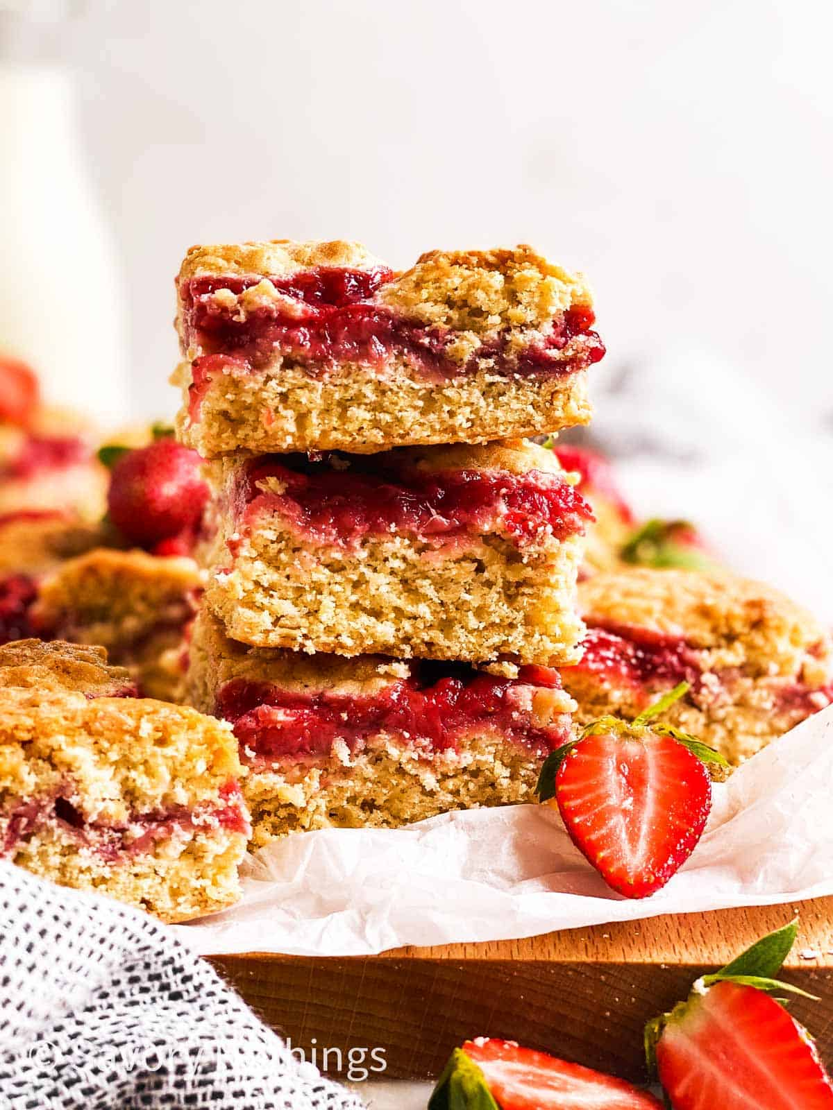 stack of three strawberry oatmeal bars on wooden board line with white baking parchment, surrounded by fresh strawberries
