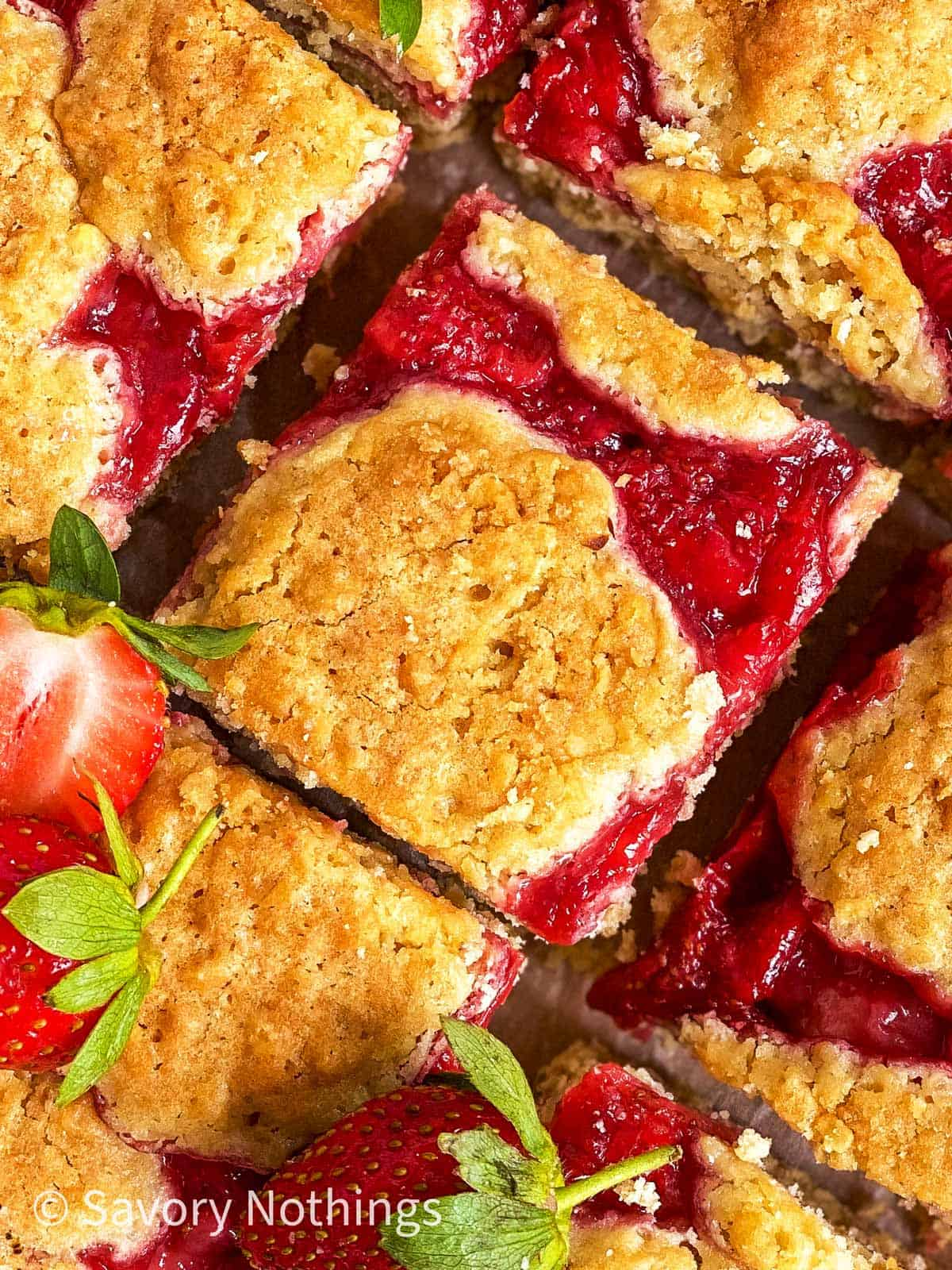 overhead close up view of sliced strawberry oatmeal bars garnished with fresh strawberries