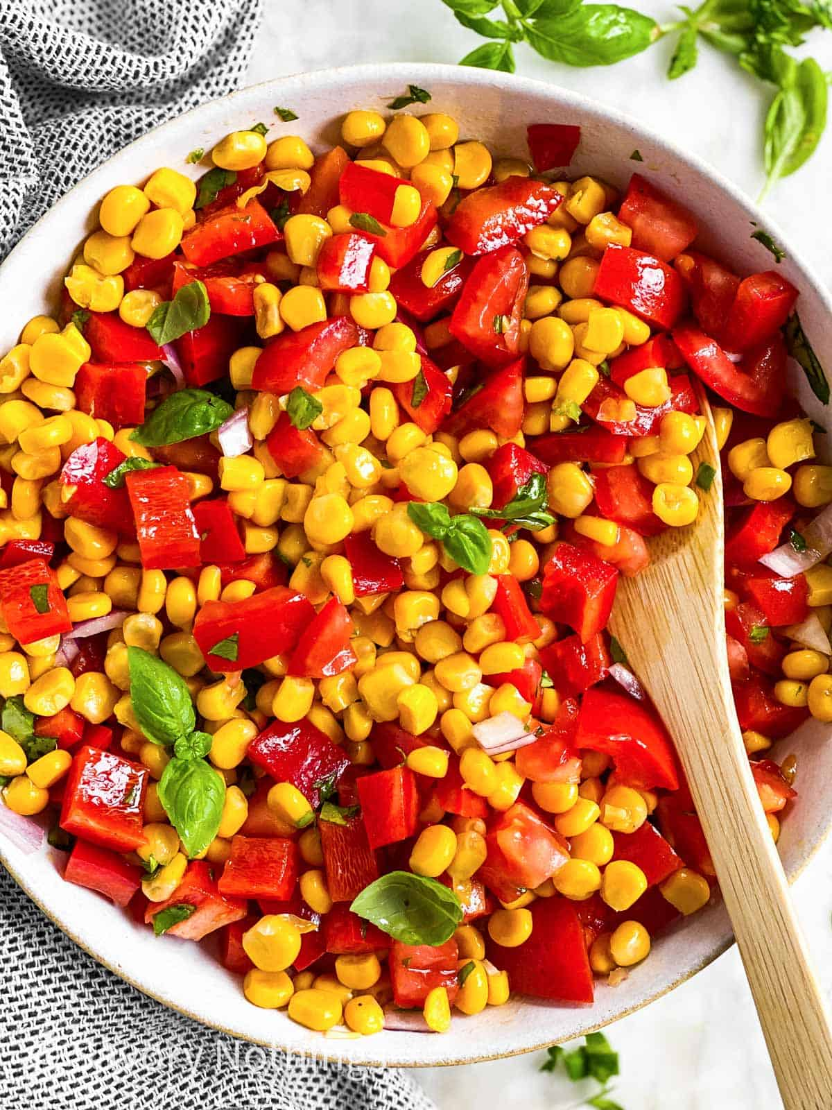 overhead close up view of summer corn salad in white bowl with wooden spoon