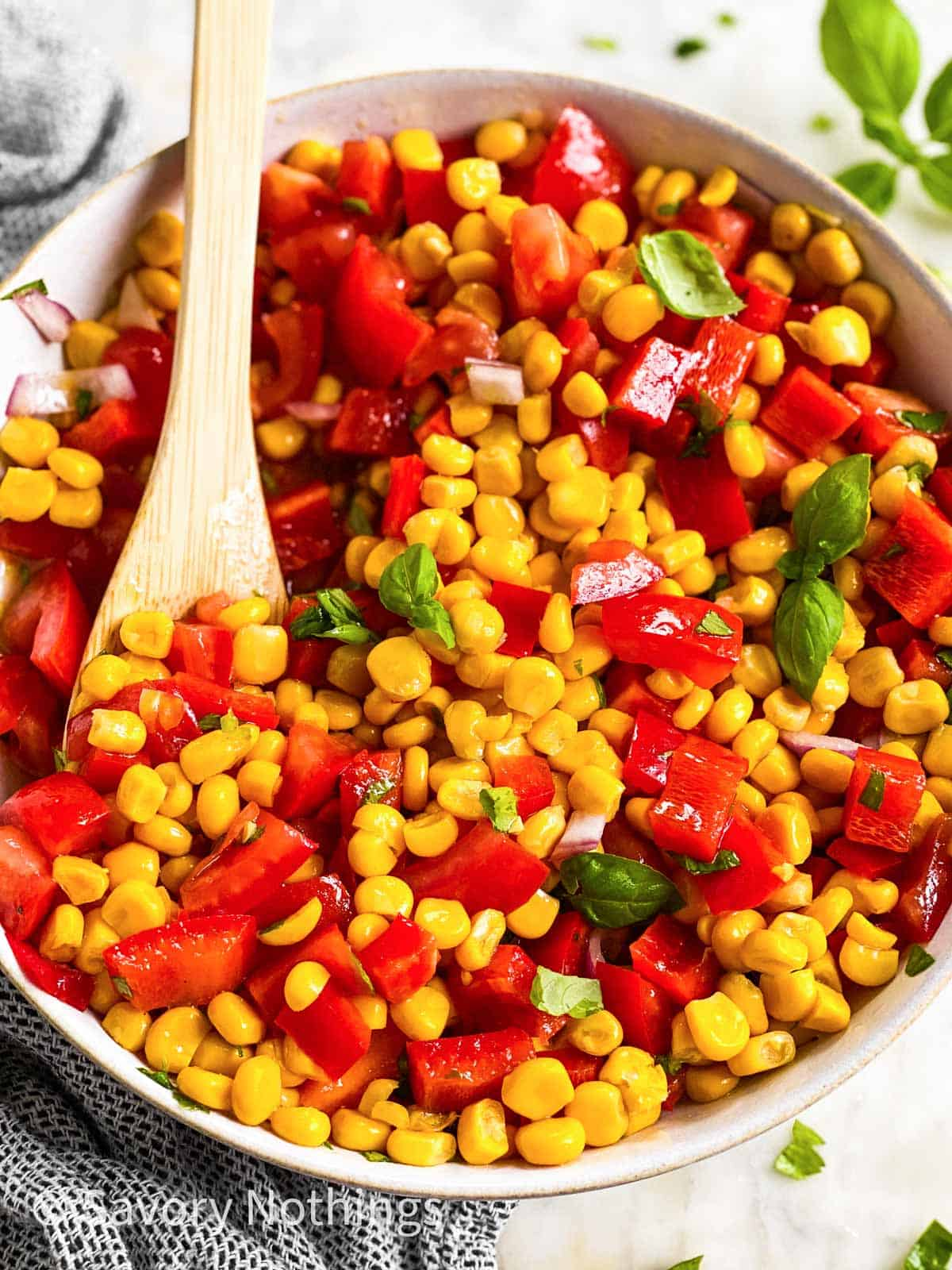 close up photo of wooden spoon in bowl with corn salad
