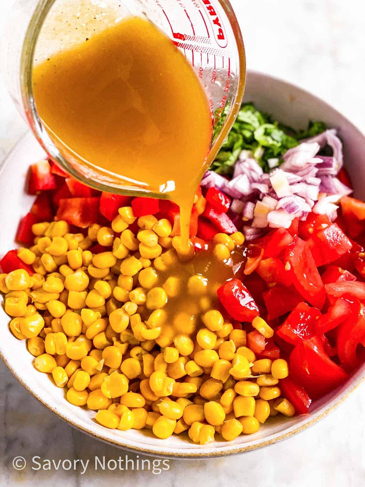 salad dressing pouring from glass measuring jug over corn salad ingredients in white bowl