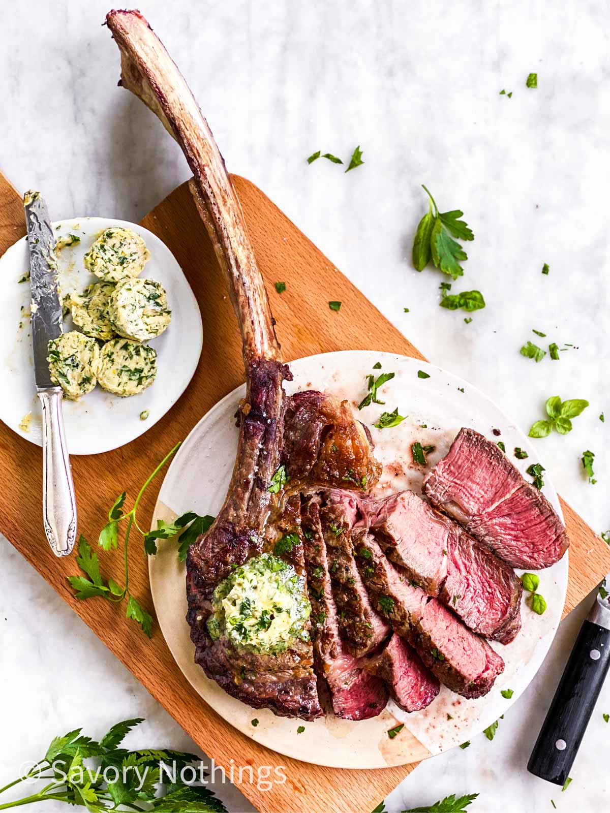 overhead view of sliced tomahawk steak on wooden board with garlic herb butter and fresh parsley