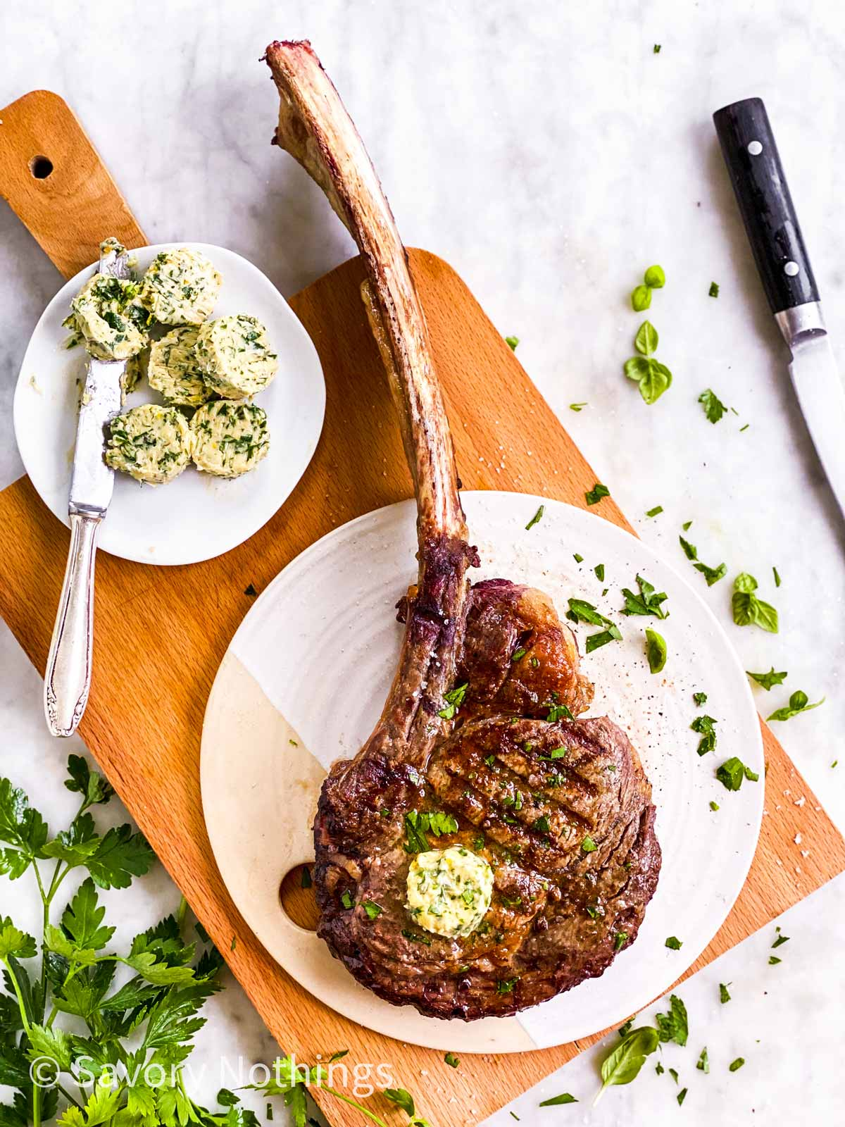 grille tomahawk steak on white platter sitting on wooden board, surrounded by steak knife, fresh parsley and garlic butter