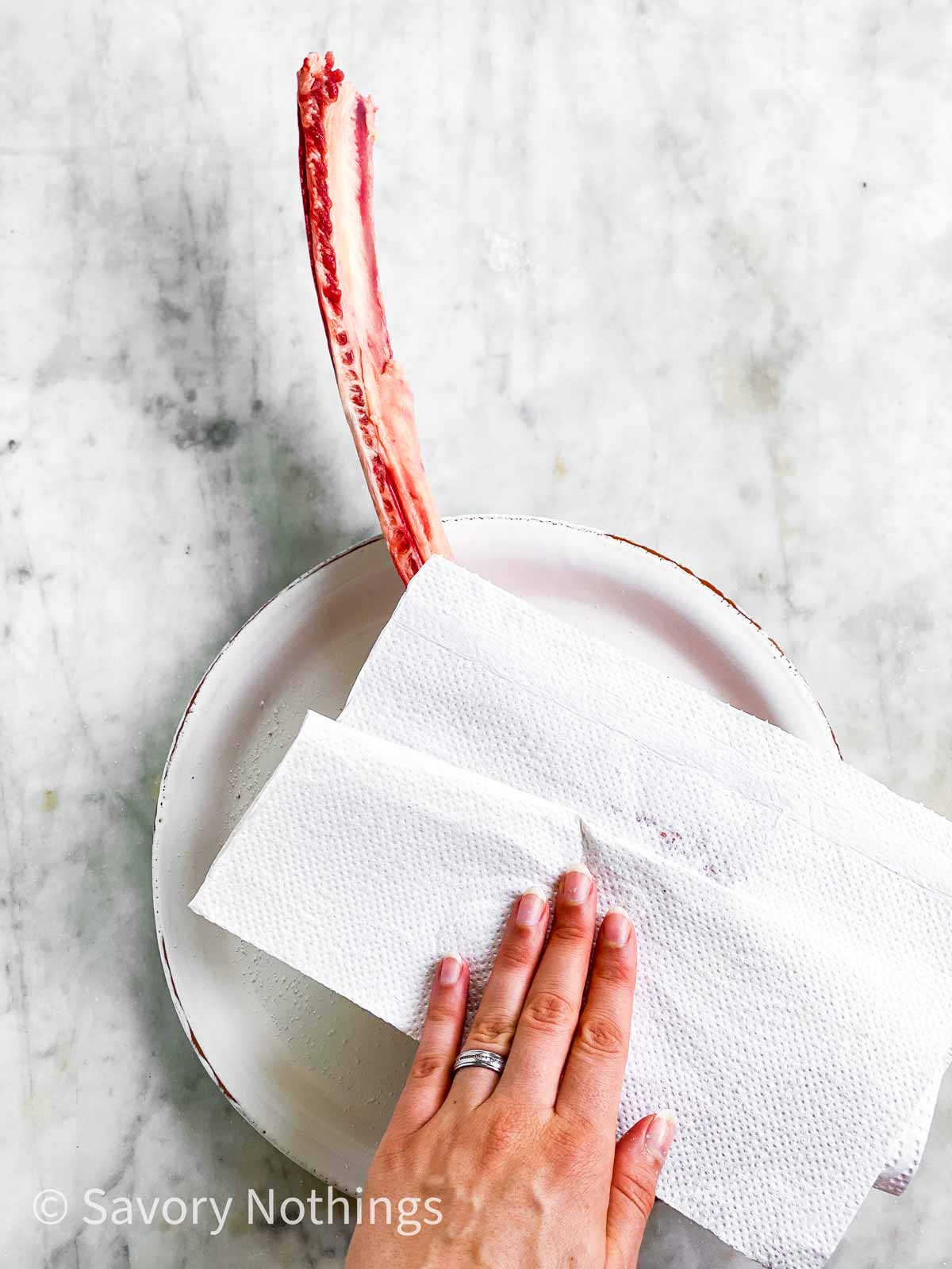 female hand using paper towels to pat dry a tomahawk steak on a white plate