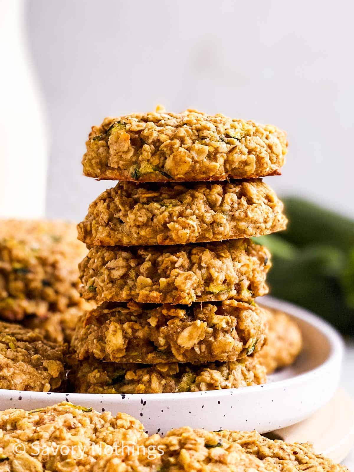 stack of zucchini bread breakfast cookies on white plate in front of milk bottle and fresh zucchini