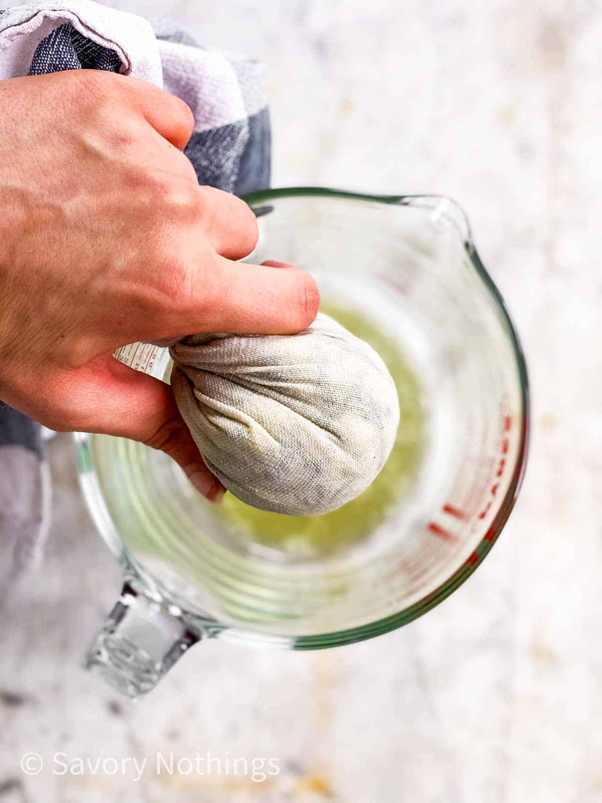 female hand squeezing zucchini in white kitchen towel over glass measuring jug