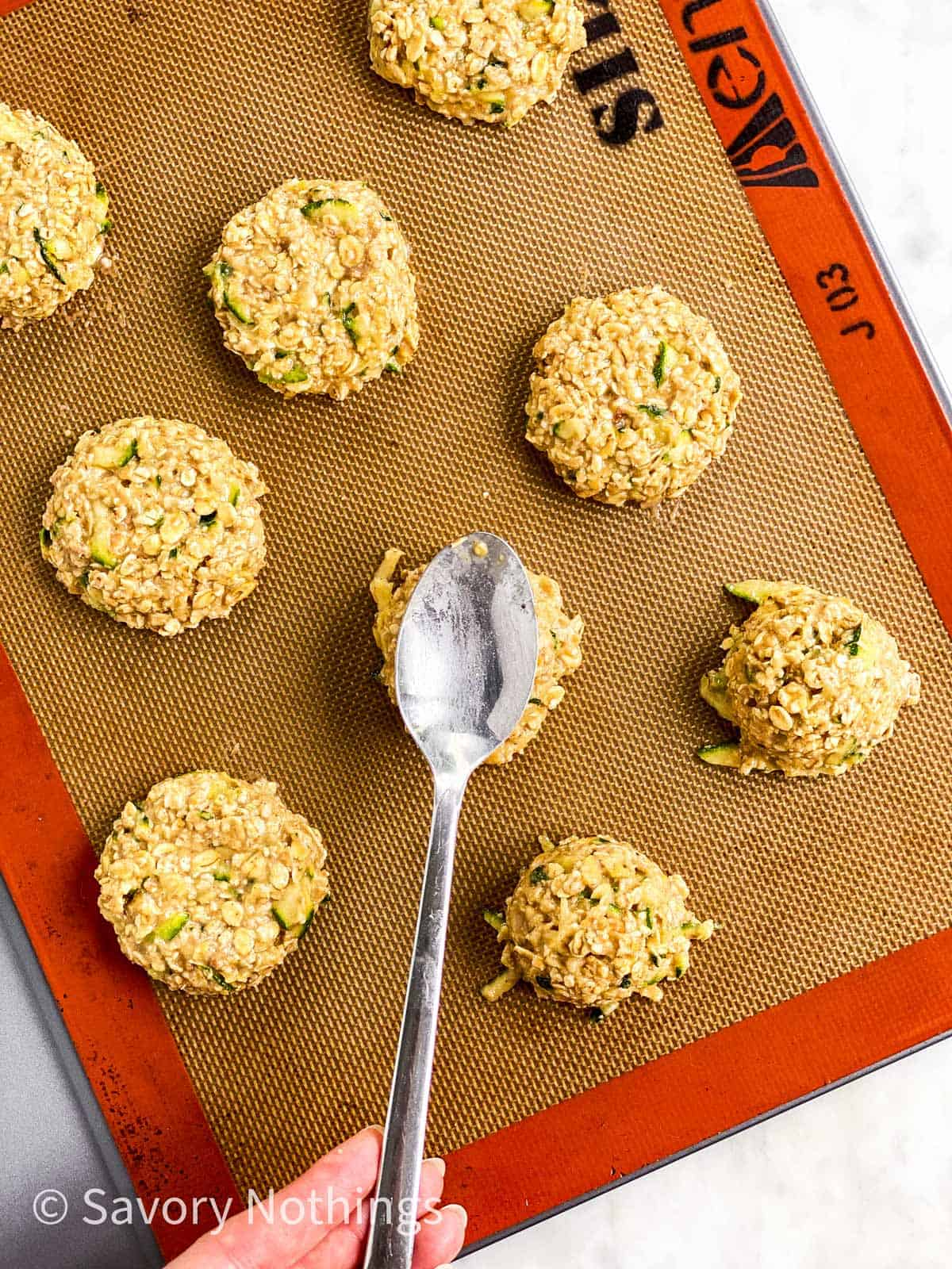 female hand using tablespoon to flatten zucchini breakfast cookies on silicone mat lined cookie sheet